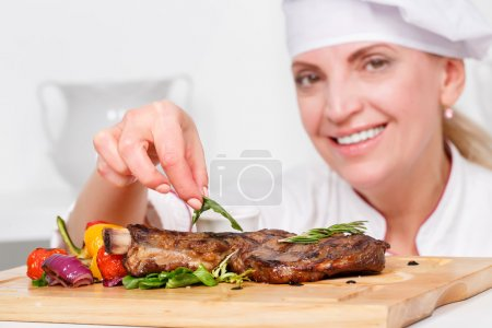 Cook   putting  rosemary on meat steak