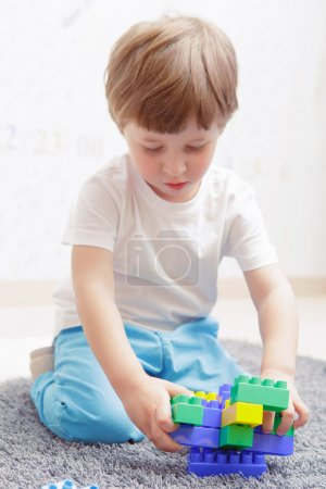 Boy plays with building kit