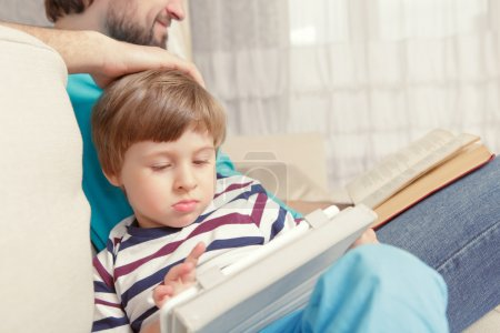 Photo for Digital age. Close-up of a small boy using a tablet device spending time together with his father - Royalty Free Image