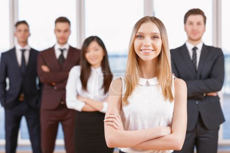 Photo for Team in the office. Young blond businesswoman standing in the foreground smiling and holding her arms crossed, her team of co-workers in the background - Royalty Free Image