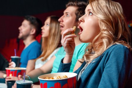 Excited woman with popcorn in cinema