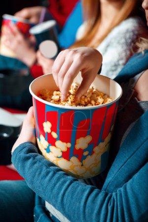 Photo pour Tellement savoureux. Fermez-vous vers le haut de la femme prenant le maïs éclaté hors de la boîte dans le cinéma - image libre de droit