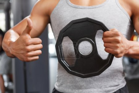 Weightlifter holding disk with thumbs up