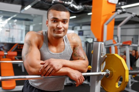 Muscular weightlifter leaning on barbell in gym