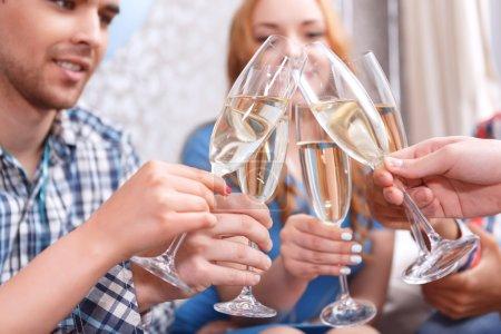 Photo pour Fête. Les jeunes décrochent des verres de champagne célébrant l'anniversaire de leur ami sélectif focus - image libre de droit