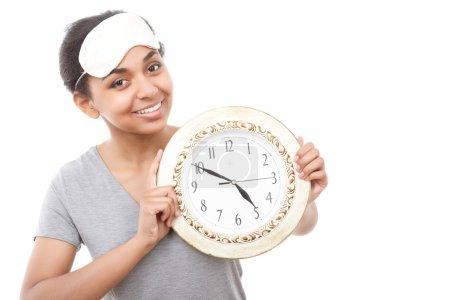 Pretty mulatto girl posing with clock