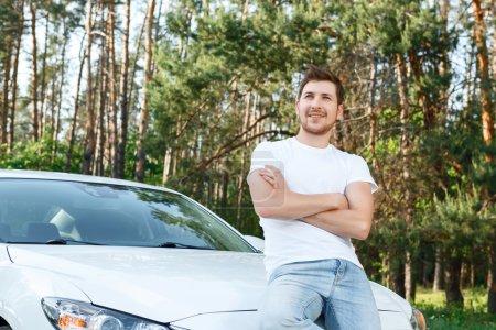 Photo pour Totalement confiant. Beau jeune homme assis sur le capot de nouvelle voiture blanche avec les bras croisés dans la région de la poitrine - image libre de droit