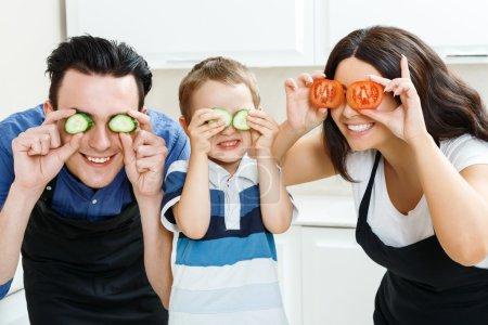 Photo pour La recherche ludique. sourire joyeux membres de la famille playin avec leur nourriture dans la cuisine - image libre de droit