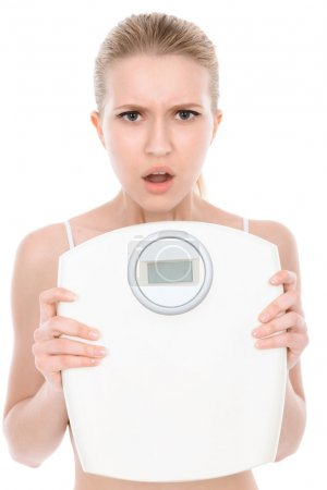 Photo for Portrait of a beautiful young blond fit girl wearing white bra standing holding a weighing-machine in her hands looking dissatisfied, isolated on a white background, waist up - Royalty Free Image