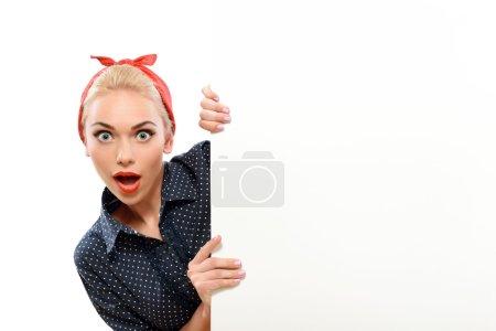 Photo pour Verticale d'une belle fille blonde de pin up avec la queue de cheval et le bandana rouge utilisant une robe pointillée bleue regardant étonné derrière un espace de copie, d'isolement sur le fond blanc - image libre de droit