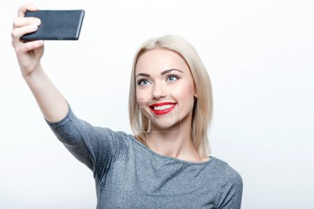 Photo for Selfie time. Young smiling blond-haired lady doing selfie on isolated white background - Royalty Free Image