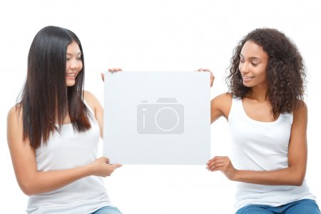 Photo for Forever together. Two pretty young ladies holding white board and looking at it while sitting on the box - Royalty Free Image