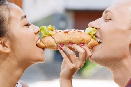 Man and woman biting same hotdog
