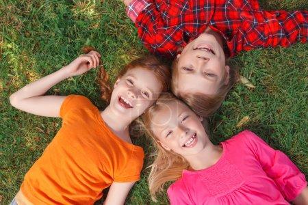 Photo pour Hé ! Ami souriant joyeux couché sur l'herbe verte et s'amusant dans la cour - image libre de droit