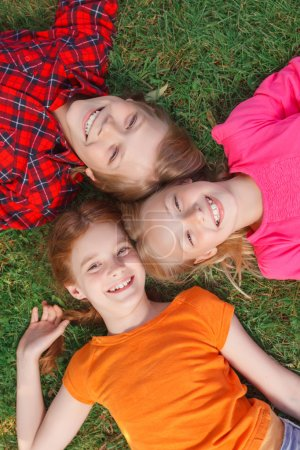 Top view of children lying on the grass