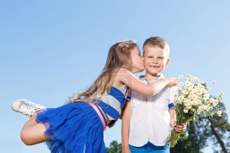 Pleasant little boy and girl kissing.