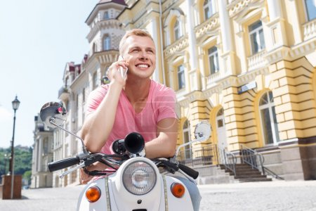 Handsome man doing selfie on scooter