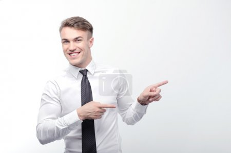 Smiling businessman pointing with fingers aside