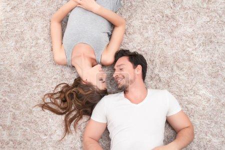 Photo pour Tous les jours ensemble. Vue du dessus du jeune couple positif souriant et se regardant tout en étant couché sur le tapis - image libre de droit