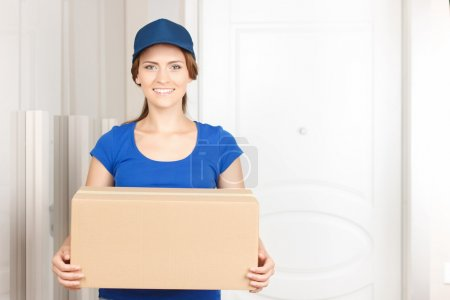 Nice deliverywoman standing near door