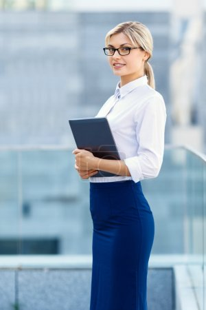 Upbeat businesswoman holding laptop