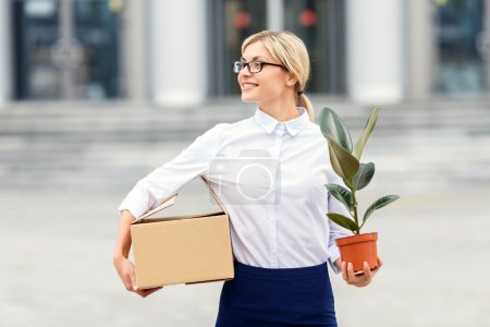 Nice businesswoman holding flower in a pot