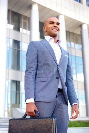 Positive businessman holding case