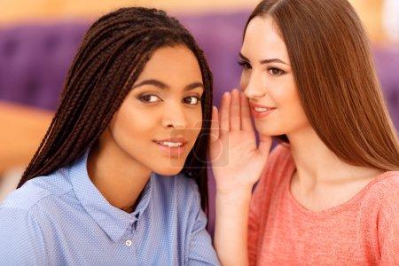 Photo pour Révèle un secret. Jolies jeunes filles heureuses assises dans le café et racontant des commérages tout en se reposant - image libre de droit