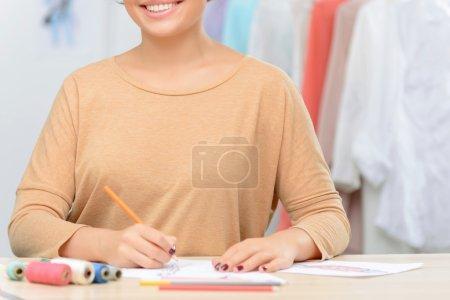 Foto de Encuentra inspiración. Agradable diseñador encantador positivo sosteniendo lápiz y haciendo dibujo mientras se siente eufórico - Imagen libre de derechos