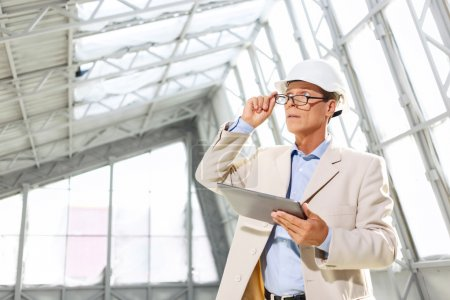 Photo for Make the progress. Professional agreeable architect keeping his glasses and holding laptop while looking up - Royalty Free Image