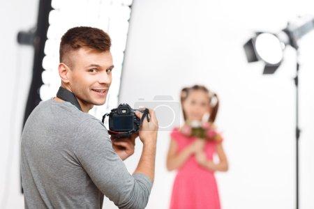 Photo pour Un moment jubilatoire. Beau photographe professionnel masculin sourit radieusement avant de reprendre son travail avec une petite fille - image libre de droit