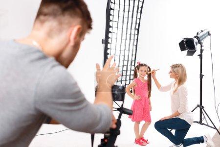 Photo pour Maquillage pour enfants. La petite fille se tient avec sa main sur le côté tandis que le maquillage simple est appliqué par professionnel - image libre de droit