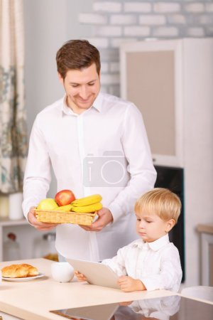 Father carrying fruits and son with digital tablet.