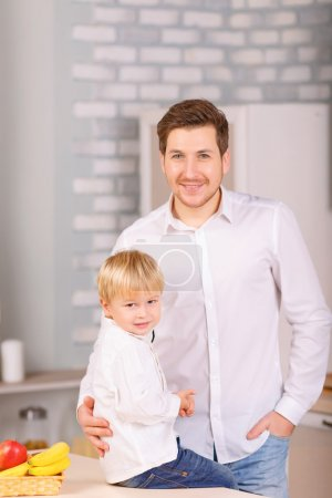 Photo pour Image parfaite. Père et son petit fils posent tous les deux dans la cuisine et sourient sincèrement - image libre de droit