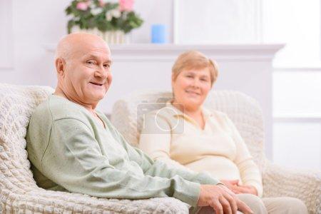 Photo pour Pour toujours ensemble. Agréable couple d'adultes aimant assis dans le fauteuil et faisant preuve de joie tout en se relaxant à la maison - image libre de droit