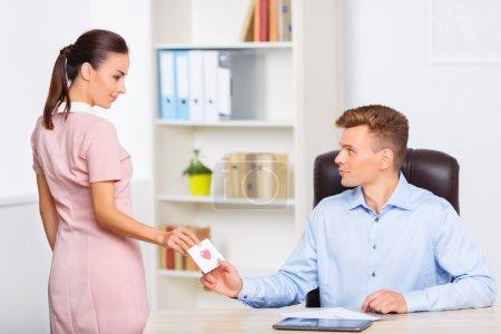 Photo pour Note secrète. Jeune femme attrayante s'arrête au bureau pour transmettre une note d'amour à son partenaire romantique - image libre de droit