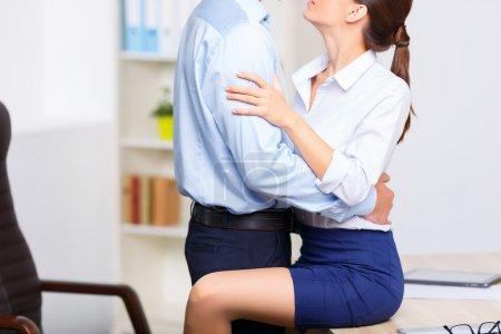 Office couple embracing each other heartily.