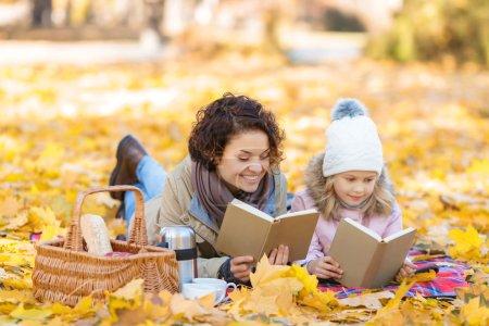 Foto de Buen fin de semana. Agradable sonrisa alegre madre e hija disfrutando leyendo libros y tumbado en la manta mientras pasar gran tiempo en el Parque - Imagen libre de derechos