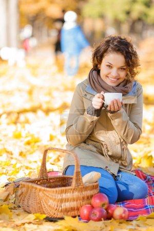 Happy woman drinking tea in park