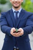 Pleasant businessman holding ground in hands