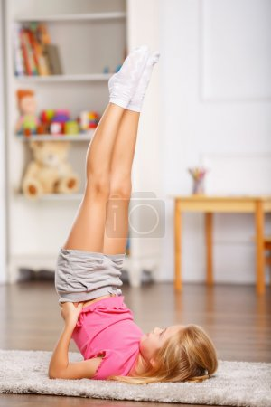 Photo for Physically active. Little schoolchild is thoroughly doing physical exercises - Royalty Free Image