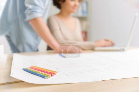 Foto de Herramientas creativas. Primer plano de crayones de colores y modelo de proyecto grande acostado en el escritorio - Imagen libre de derechos