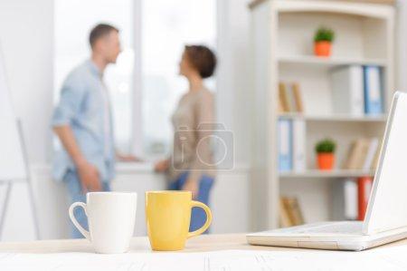 Foto de Pausa en el trabajo. Dos colegas están charlando cerca de la ventana mientras sus copas de colores y su portátil descansan en el escritorio - Imagen libre de derechos