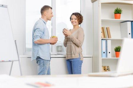 Foto de Descanso. Dos colegas alegres de pie cerca de la ventana mientras beben té y conversan - Imagen libre de derechos