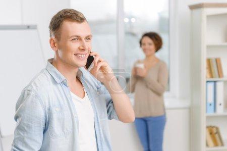 Foto de Una charla importante. Hombre guapo haciendo una llamada mientras su colega bebe café junto a la ventana - Imagen libre de derechos