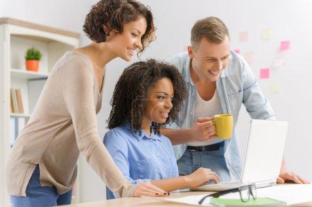 Foto de Trabajo en equipo bien planeado. Tres jóvenes colegas creativos están poniendo en orden sus tareas - Imagen libre de derechos