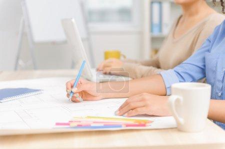Foto de Ocupado con tareas. Dos jóvenes empleados de oficina están sentados en el escritorio y ambos ocupados con trabajos creativos de construcción - Imagen libre de derechos