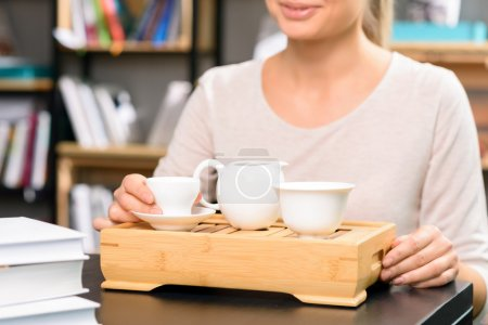 Woman has teatime in the library