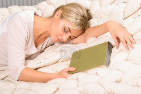 Young woman falls asleep while reading.