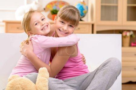 Pleasant sisters embracing